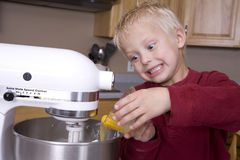Boy pouring eggs into mixer Royalty Free Stock Images