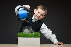 Boy pouring home model and green grass Stock Photography