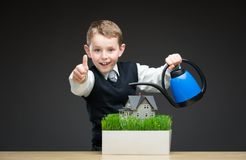Boy pouring house model and green grass Royalty Free Stock Image