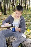 Boy pouring tea from thermos to cup Stock Photography