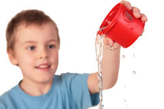 Boy  pours out water. From red plastic cup Royalty Free Stock Photo