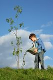 Boy pours on seedling of tree by water Stock Photo