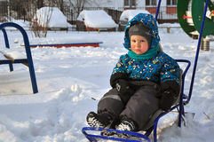 The boy with pouted sits in the sledge stock image