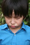 Boy pouting. Little boy in blue shirt showing angry face in the park Stock Photo