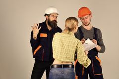 Boy Powered. Issues face boys. Misunderstanding concept. Brigade of workers, builders in helmets, repairers, lady. Arguing, discussing contract, grey background Royalty Free Stock Images