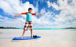 Boy practice surfing at beach Stock Photos