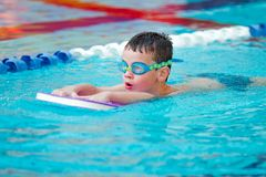 Boy Practice Swimming. Child is practicing swim in pool with googles Royalty Free Stock Image