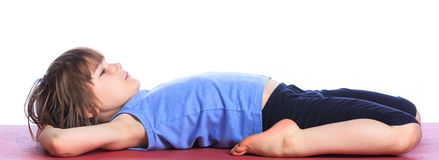Boy practice yoga. Cute little boy practice yoga. Isolated on the white background Royalty Free Stock Images