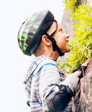 Boy practicing climbing outdoor on the stone wall Stock Images