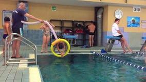 Boy practicing dip into the pool water through hoop. stock video footage