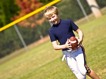 Boy Practicing Football. A young boy on the field practicing for a football game. 10 years old royalty free stock photography
