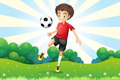 A boy practicing soccer at the hilltop Stock Images