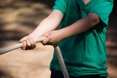 Boy practicing tug of war during obstacle course training in the boot camp Royalty Free Stock Photos