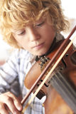 Boy Practicing Violin At Home Stock Image