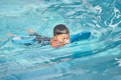 Boy practise swimming with foam pad floater in water royalty free stock photography