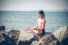 Boy practising yoga on beach Stock Photos