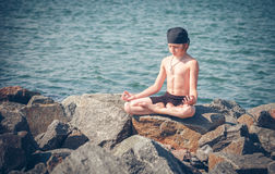 Boy practising yoga on beach Stock Image