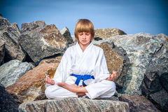 Boy practising yoga on beach Royalty Free Stock Photos