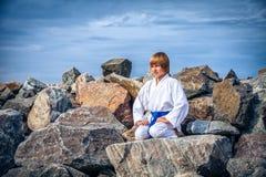 Boy practising yoga on beach Stock Image