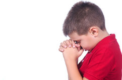 Boy praying. Praying child with red sweater on a white background Stock Photo