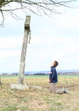 Boy praying by cross with Jesus. Kid - little boy kneeing and praying by a cross with crucified Jesus in meadows Stock Photography