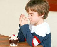 Boy Praying Before Dessert Stock Photo