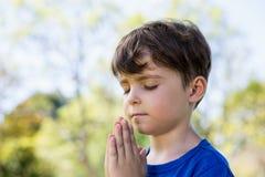 Boy praying with eyes closed. Close-up of boy praying with eyes closed in park royalty free stock image
