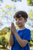 Boy praying with eyes closed. In park royalty free stock photos