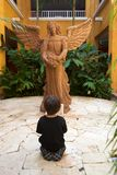 Boy praying in front of an angel. Boy down on his knees and praying in front of an angel statue Royalty Free Stock Photography