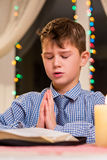 Boy praying at the table. Kid prays at nighttime. Christmas prayer at city church. Youthful parishioner on Christmas Royalty Free Stock Photo