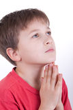 The boy prays. Has prayerfully combined hands before itself Royalty Free Stock Photos