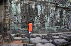 Boy prays at the Buddha wall in Cambodia Stock Photos