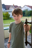 Boy Pre-teen Confident Open Door Handle. A pre-teen boy opens a door with his hand on the handle, a confident expression on his face. Suburban yards and roofs in stock images