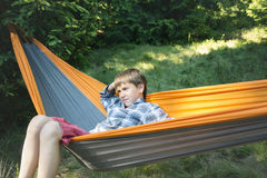 Boy with a preoccupied face is swinging in a hammock Royalty Free Stock Photography