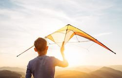Boy prepare start to fly a kite over the sunset mountain hills stock photo
