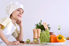 Boy prepares a dish. Cute boy prepares a dish of vegetables in the kitchen Royalty Free Stock Photos