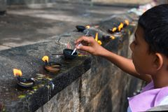 Boy prepares oil lamp to set fire it in an offerings place of th. DAMBULLA, SRI LANKA - NOV 2016: Boy prepares oil lamp to set fire it in an offerings place of Stock Images