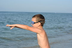 Boy prepares to dive. A young school boy prepares to jump in the sea to dive with glasses royalty free stock photography