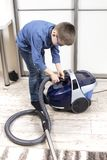 The boy prepares a vacuum cleaner to clean the flat.