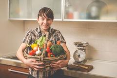 Boy prepares vegetables in the kitchen Royalty Free Stock Photos