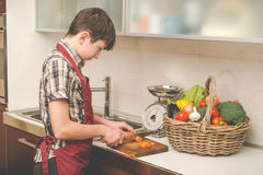 Boy prepares vegetables in the kitchen Royalty Free Stock Photography