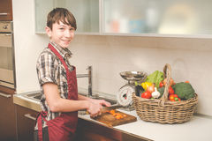 Boy prepares vegetables in the kitchen Stock Image