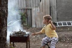 Boy preparing barbecue Royalty Free Stock Photos