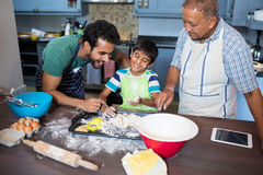 Boy preparing food while standing with father and grandfather. In kitchen at home Royalty Free Stock Images