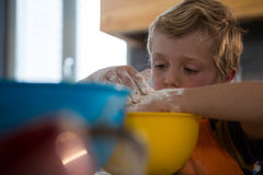 Boy preparing food in yellow container. At kitchen counter Stock Photos