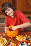 Boy preparing for Halloween - carving a jack-o-lantern. Boy preparing for Halloween - carving a pumpkin jack-o-lantern outdoors Royalty Free Stock Photography