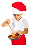 Boy preparing macaroni with tomatoes Stock Image