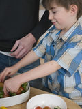 Boy Preparing Salad With Father At Kitchen Counter Royalty Free Stock Photos
