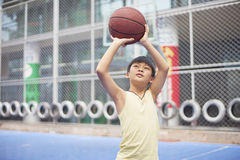 Boy preparing for shooting at basketball court Stock Images