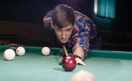 Boy preparing for shot the billiard ball. Boy in focus aiming for shot the billiard ball which aren't in focus Stock Images